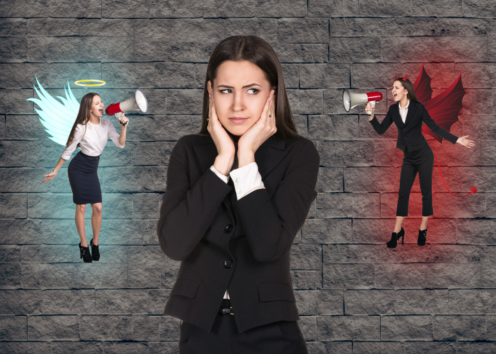 Young troubled businesswoman making choice between good and bad on grey brick background